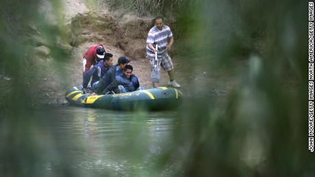 MCALLEN, TX - JANUARY 04:  A smuggler (R), pushes off a raft of undocumented immigrants to cross the Rio Grande from Mexico into the United States on January 4, 2017 near McAllen, Texas. The number of incoming immigrants has surged in advance of President-elect Donald Trump's inauguration January 20. He has pledged to build a wall along the U.S.-Mexico border.  (Photo by John Moore/Getty Images)