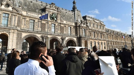 """People stand in front of the Louvre museum on February 3, 2017 in Paris after a soldier has shot and gravely injured a man who tried to attack him.""""Serious public security incident under way in Paris in the Louvre area,"""" the interior ministry tweeted on February 3 as streets in the area were cordoned off to traffic and pedestrians.  / AFP / ALAIN JOCARD        (Photo credit should read ALAIN JOCARD/AFP/Getty Images)"""
