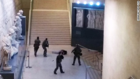 A picture taken by a tourist on a mobile phone shows a soldier opening fire at an entry to the Louvre.