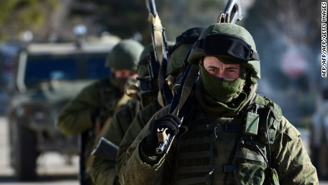 Armed men, believed to be Russian servicemen, patrol outside an Ukrainian military base in Perevalnoye on March 17, 2014. The United States and Europe aimed sanctions directly at Vladmir Putin's inner circle Monday to punish Russia's move to annex Crimea, deepening the worst East-West rift since the Cold War. The move came hours after the Ukrainian regime voted to join Russia in a referendum the West deems illegitimate and as Crimea embarked on the next political steps to embrace Kremlin rule. AFP PHOTO/ VASILY MAXIMOV        (Photo credit should read VASILY MAXIMOV/AFP/Getty Images)