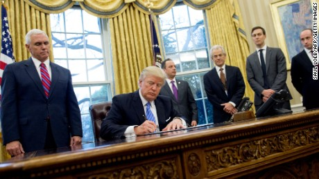 US President Donald Trump signs an executive order alongside White House Chief of Staff Reince Priebus (C), US Vice President Mike Pence (L), National Trade Council Advisor Peter Navarro (3rd R), Senior Advisor Jared Kushner (2nd R) and Senior Policy Advisor Stephen Miller in the Oval Office of the White House in Washington, DC, January 23, 2017.