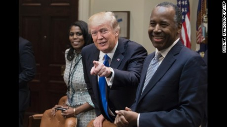 United States President Donald J. Trump (C), gestures beside Director of Communications for the Office of Public Liaison Omarosa Manigault (L) and nominee to lead the Department of Housing and Urban Development (HUD) Ben Carson (R), after arriving for a meeting on African American History Month in the Roosevelt Room of the White House in Washington, DC, USA, 01 February 2017. Credit: Michael Reynolds / Pool via CNP - NO'WIRE'SERVICE - Photo by: Michael Reynolds/picture-alliance/dpa/AP Images