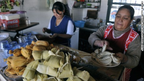 Tamales (ground maize with meat wrapped in a maize leaf) and humitas (flavored corn paste wrapped in corn leaves) are displayed in a bar as women prepare empanadas (meet pasty) at a typical eating place in Salta, at the foothills of the Andes mountain range, in the Argentine northern province of Salta, on June 14, 2009. The city of Salta, a tourist attraction due to its colonial architecture and surrounding valleys, has about 500.000 inhabitants and was founded on April 16, 1582 by Spaniard Hernando de Lerma.  AFP PHOTO/JUAN MABROMATA (Photo credit should read JUAN MABROMATA/AFP/Getty Images)
