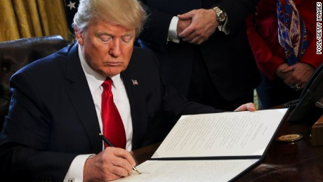 U.S. President Donald Trump signs Executive Orders in the Oval Office of the White House, including an order to review the Dodd-Frank Wall Street to roll back financial regulations of the Obama era February 3, 2017 in Washington, DC.