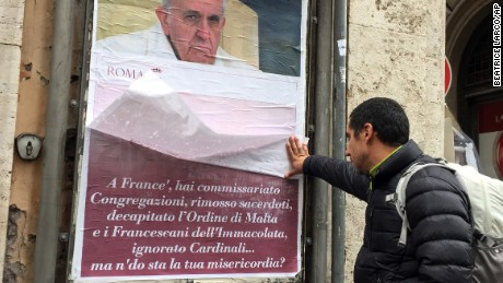 """A passerby lifts a paper sheet covering an anti-Pope Francis poster to read it, in central Rome, Saturday, February 4, 2017. The posters appeared around Rome featuring a stern-looking Francis and questioning """"Where's your mercy?"""" It referenced the """"decapitation"""" of the Knights of Malta, Cardinal Raymond Burke's marginalization and other actions Francis has taken against conservative, tradition-minded groups."""