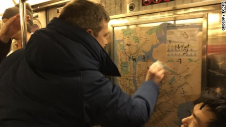 Chef Jared Nied scrubs graffiti from the subway car Saturday night.
