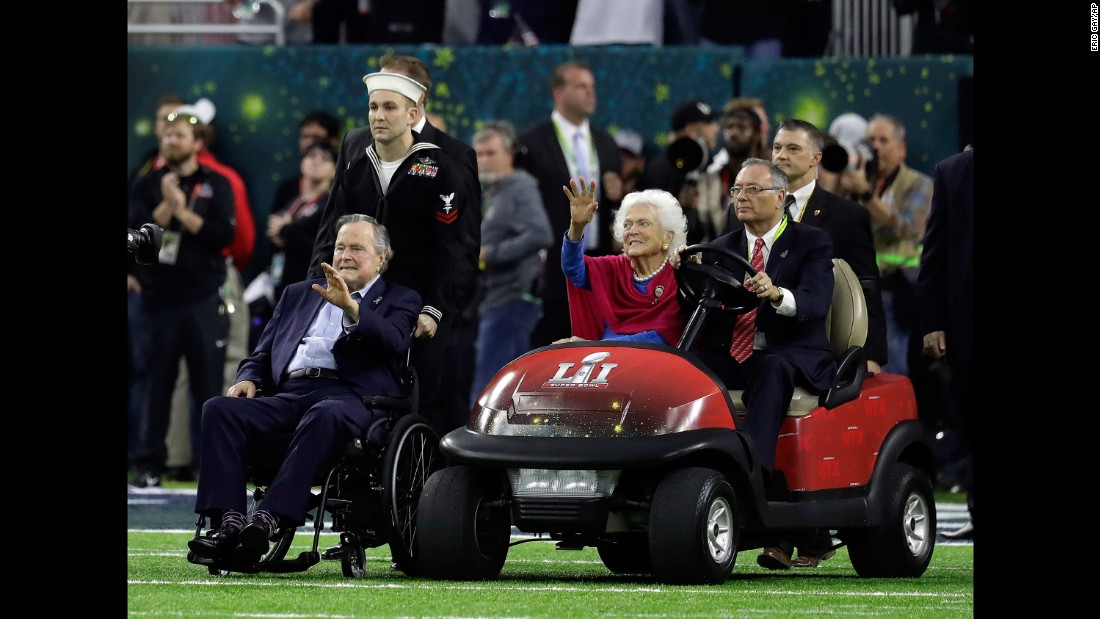 "Former President George H.W. Bush and his wife, Barbara, wave as they arrive for the pregame coin toss. <a href=""http://www.cnn.com/2017/01/30/politics/former-president-george-h-w-bush-released-from-hospital/"" target=""_blank"">They were both recently hospitalized.</a>"