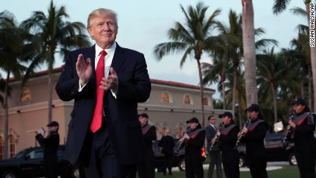 President Donald Trump listens to the Palm Beach Central High School Band as they play at his arrival at Trump International Golf Club in West Palm Beach, Florida Sunday, February 5, 2017.