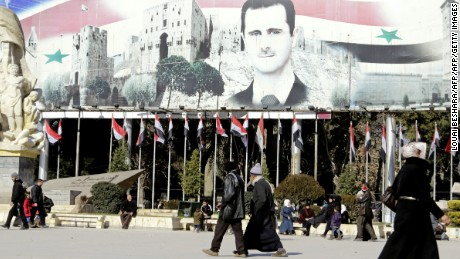 Syrians walk past a poster of  President Assad in Aleppo.
