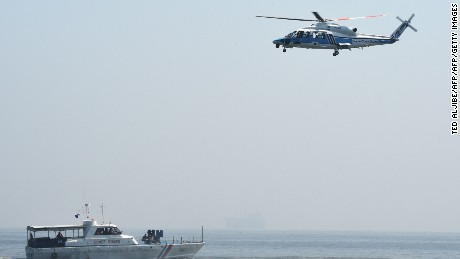 "A helicopter from Japanese Coast Guard ship PLH02 Tsugaru hovers above a Philippine Coast Guard boat with its personnel as mock pirates during their annual anti-piracy exercise in the waters off Manila Bay on July 13, 2016, a day after a UN-backed tribunal declared China has no ""historic rights"" in the South China Sea.  China warned of ""conflicts and confrontation"" in the South China Sea as it angrily rejected July 13 an international tribunal's verdict that its claims to most of the strategically vital waterway had no legal basis. / AFP / TED ALJIBE        (Photo credit should read TED ALJIBE/AFP/Getty Images)"