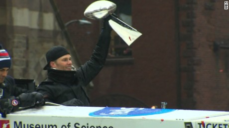 New England Patriots quarterback Tom Brady holds a fifth Super Bowl trophy aloft Tuesday in Boston.