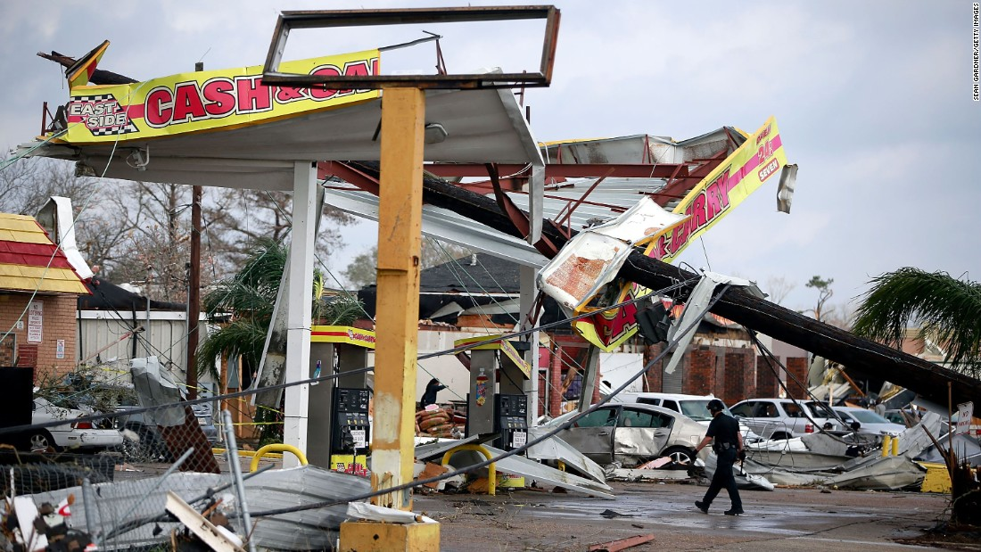 A police officer walks through a damaged gas station along Chef Menteur Highway.