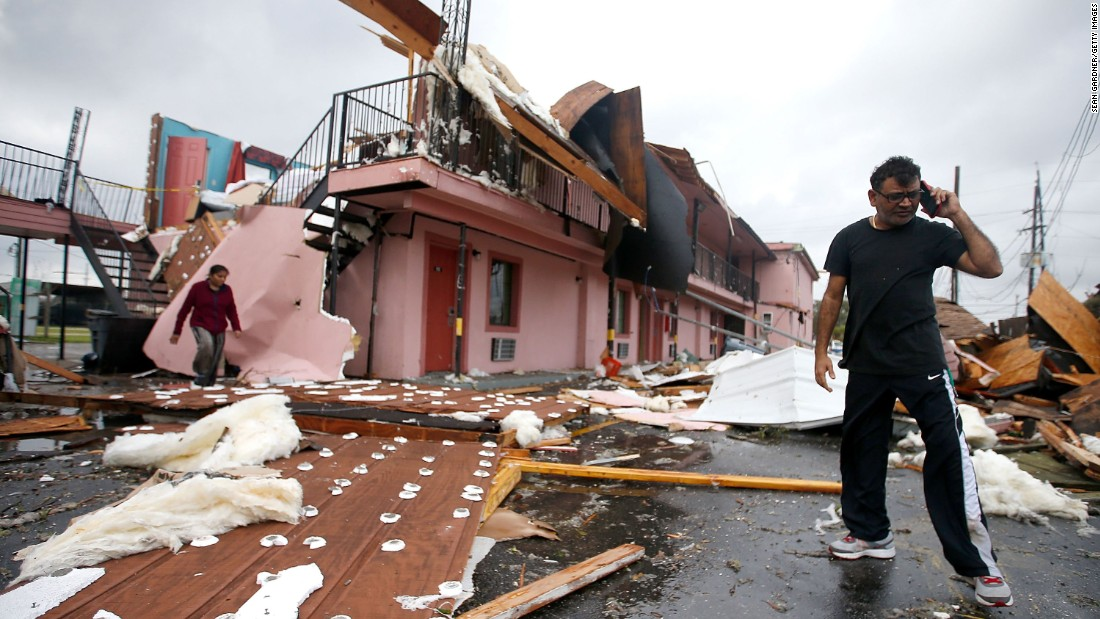 A man talks on the phone amid the debris of a motel.