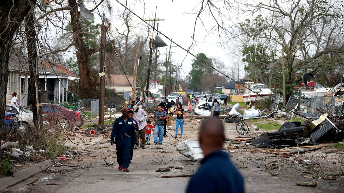People walk down a street in New Orleans after a tornado touched down in the eastern part of the city on Tuesday, February 7.