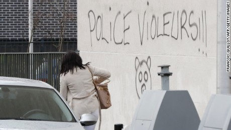 "A woman walks next to graffiti reading ""police rapists."""