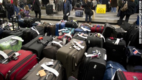 Unclaimed bags in the foreground as travelers retrieve their luggage at New York's LaGuardia Airport on December 28, 2010. The US northeast began to shake off the icy grip of one of the biggest blizzards in years, but beleaguered travelers faced at least another day of headaches in New York airports.      AFP PHOTO/DON EMMERT (Photo credit should read DON EMMERT/AFP/Getty Images)