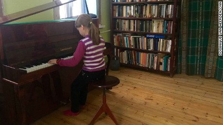 Mariika Savkevich plays the piano at her home in Avdiivka, while Ukraine's war rages nearby.