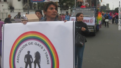 Luis Alberto Rojas Marin marches in a parade in Lima, Peru, holding up a sign for an LGBT non-profit.