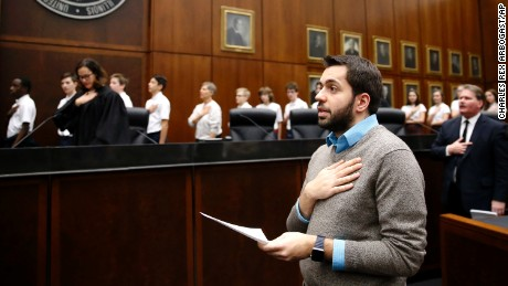 Rohi Atassi, right, from Syria, leads new US citizens in the Pledge of Allegiance after Atassi and 116 others from 37 countries took the oath of citizenship from U.S. District Judge Sara Ellis, left, in the Northern District of Illinois, during a naturalization ceremony Tuesday, Feb. 7, 2017, in Chicago. Atassi has not returned to Syria since his last visit in the fall of 2011. (AP Photo/Charles Rex Arbogast)