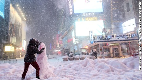 NEW YORK, NY - JANUARY 23: A woman decorates a snowman in Times Square as all cars but emergency vehicles are banned from driving on the road on January 23, 2016 in New York City. The Northeast and parts of the South are experiencing heavy snow and ice from a slow moving winter storm. Numerous deaths from traffic accidents have been reported as the storm moves up the coast.  (Photo by Yana Paskova/Getty Images)