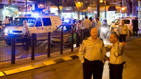 Israeli police officers inspect the scene of  the attack in Petah Tikva.