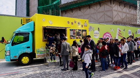 "Dubbed Pineapple Canteen, the cheerful yellow truck specializes in traditional Hong Kong pineapple buns, named for their bulbous shape and thick crown of sugar. The pastry purveyor was one of three food trucks to launch on February 3, as part of the Tourism Commission's two-year pilot program. By the end of March, 13 more foods trucks will join them, setting up in eight assigned tourism destinations around the city, including the Central Harbourfront, Hong Kong Disneyland and Ocean Park. Debuting over the Chinese New Year holiday, Pineapple Canteen sold 600 pineapple buns on its first day of operation and an estimated 2,000 by the end of the weekend. In addition to the traditional buns, the popular truck serves contemporary renditions -- filled with fresh cream and diced pineapple, or stuffed with pork chops. ""I have never operated a food truck before, but I thought it'd be a fun challenge,"" says operator Carrie Lam, who also runs a family-owned cha chaan teng diner called Tan Sing Café. ""We wanted to change up the traditional pineapple bun recipe, so we used Japanese corn meal to give it a crunchy texture outside, then we added fresh pineapple and cream for a smooth, cool taste inside."""