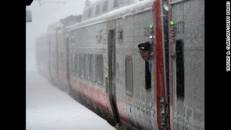 A train conductorlooks at the snow at the Metro North Greenwich train station on February 9, 2017 as  winter storms hit the area in Greenwich, Connecticut. / AFP / TIMOTHY A. CLARY        (Photo credit should read TIMOTHY A. CLARY/AFP/Getty Images)