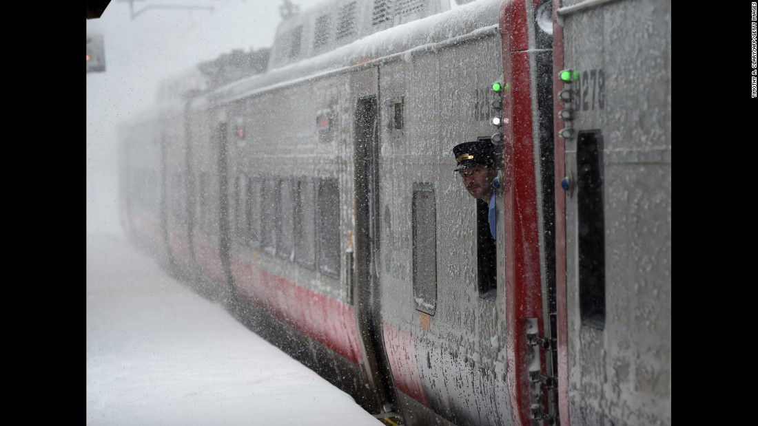 A train conductor looks at the snow in Greenwich, Connecticut.