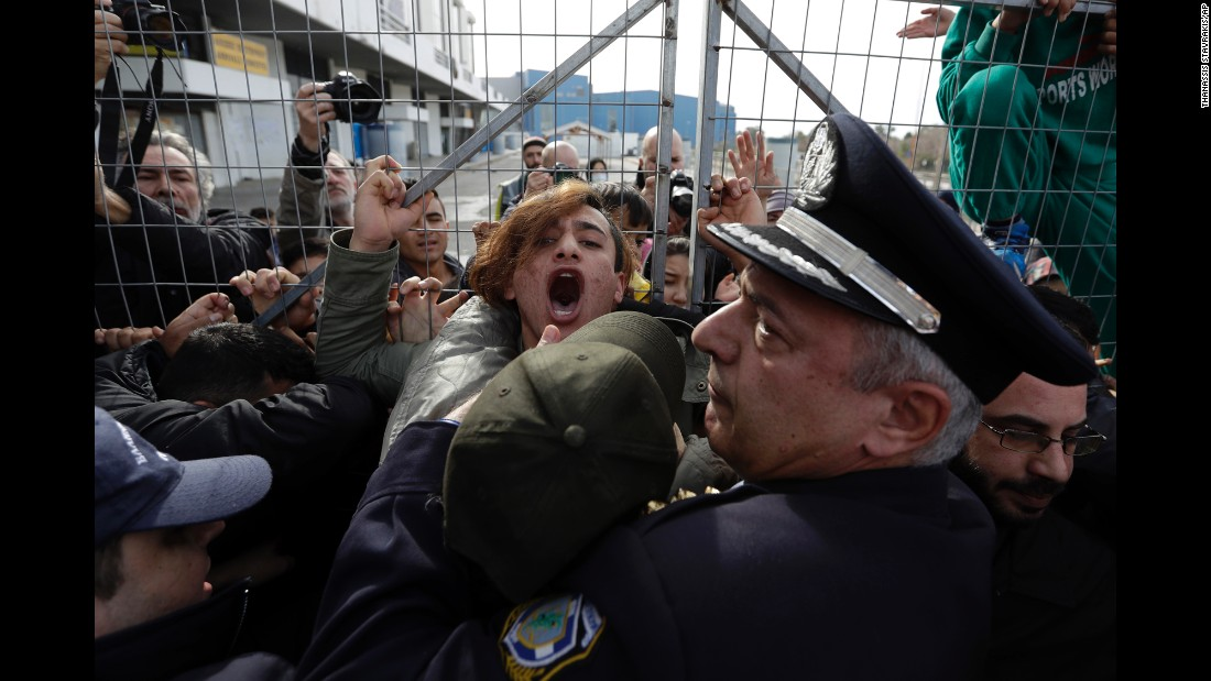 Police scuffle with Afghan migrants as they block the entrance of the Hellenikon migrant camp in Athens, Greece, on Monday, February 6. Greece says more than 60,000 people are stranded in camps after European border closures last year.
