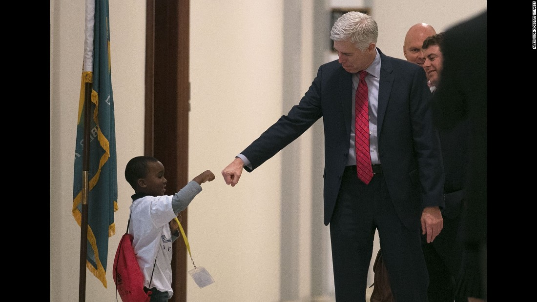 Supreme Court nominee Neil Gorsuch fist-bumps Charles Marshall III as he arrives for a meeting in Washington on Wednesday, February 8. Gorsuch has been visiting with US senators from both parties.