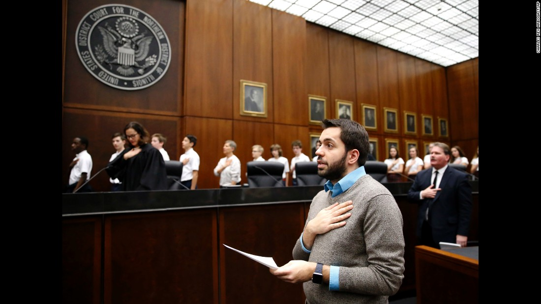 Rohi Atassi, front, leads new US citizens in the Pledge of Allegiance after he and 116 others took the oath of citizenship Tuesday, February 7, in Chicago. Atassi is from Syria.