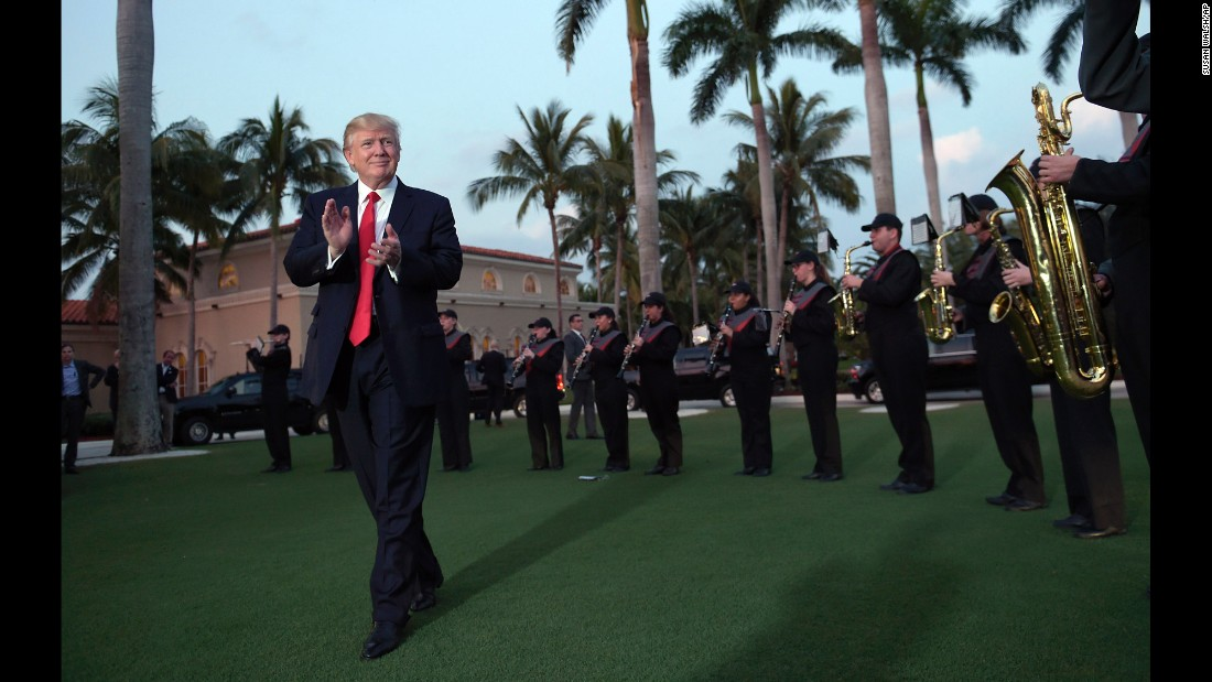 US President Donald Trump listens to a high school marching band as he arrives at the Trump International Golf Club in West Palm Beach, Florida, on Sunday, February 5.