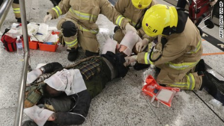 Rescue personnel attend to an injured person Friday after a fire hurt 13 on a Hong Kong metro train.