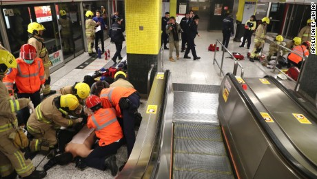 Firefighters give medical treatment to passengers Friday at Hong Kong's Tsim Sha Tsui station.