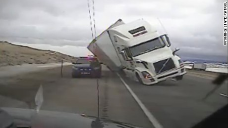 Reported gusts up to 90 miles per hour knocked a tractor trailer onto a Wyoming State Patrol cruiser near Elk Mountain, Wyoming on Tuesday.