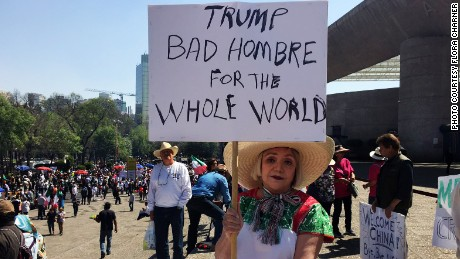 "Maria Eugenia Montes de Oca holds up a sign lambasting Trump as a ""bad hombre."""