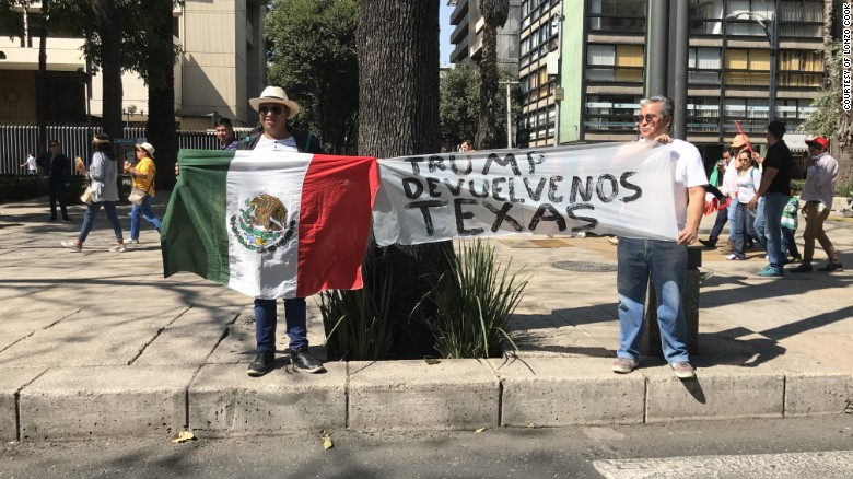 "Mexicans took to the streets Sunday to air their grievances against President Donald Trump and to protest corruption in their home country. Two men in Mexico City hold a sign that reads, ""Trump, give us Texas back."""