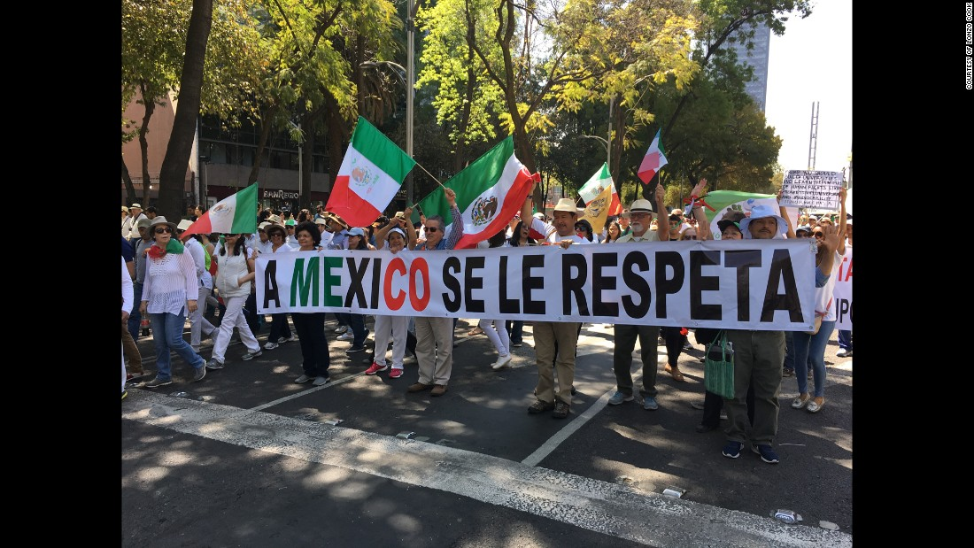 "Protesters in Mexico City march behind a banner that says ""You respect Mexico."""