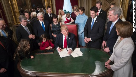 US President Donald Trump is joined by the Congressional leadership and his family as he formally signs his cabinet nominations into law, in the President's Room of the Senate, at the Capitol in Washington,DC on January 20, 2017.  From left are Senate Minority Leader Chuck Schumer, D-N.Y., Sen. Roy Blunt, R-Mo., Donald Trump Jr., Vice President Mike Pence, Jared Kushner, Karen Pence, Ivanka Trump, Barron Trump, Melania Trump, Speaker of the House Paul Ryan, R-Wis., Majority Leader Kevin McCarthy, D-Calif., House Minority Leader Nancy Pelosi, D-Calif. / AFP / POOL / J. Scott Applewhite
