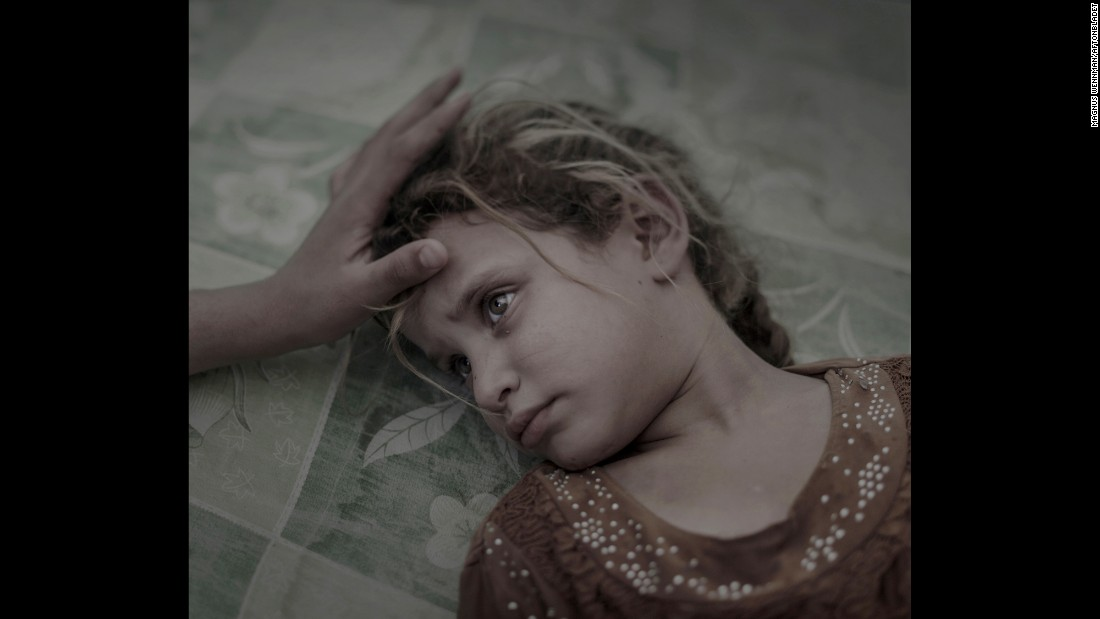 "Maha, 5, lies on a dirty mattress at a refugee camp in Iraq. She and her family fled their village because of ISIS and a lack of food. ""I do not dream, and I'm not afraid of anything anymore,"" Maha said quietly while her mother stroked her hair."
