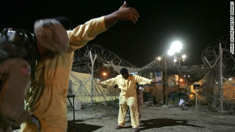 US military pat down suspected insurgents while processing new detainees at the Abu Ghraib Prison October 27, 2005 in Baghdad, Iraq.