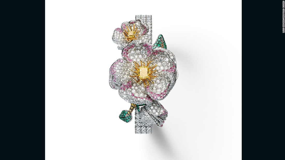 The diamond-set dial on this white and yellow gold watch is hidden beneath an elaborate flower adorned with white, yellow, cognac and gray diamonds, pink sapphires and emeralds.