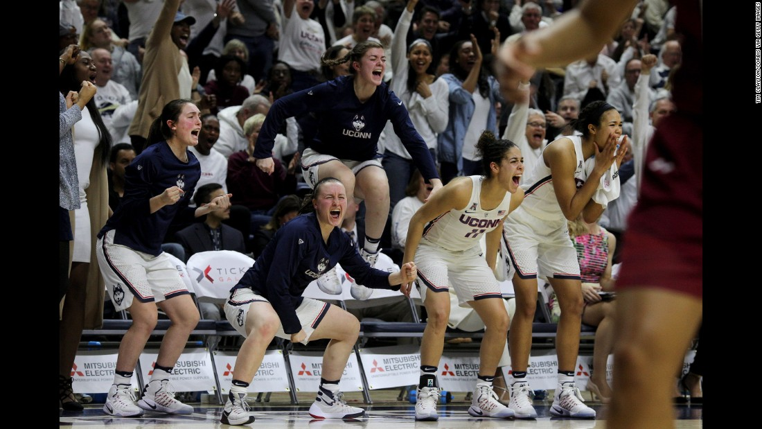 The University of Connecticut bench erupts as they  celebrate a basket during the team's 100th win on Monday, February 13.