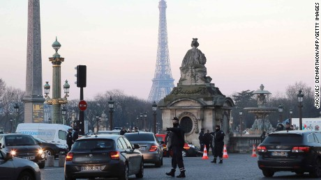 A policeman regulates traffic in Paris last month, where traffic restrictions are intended to curb emissions.