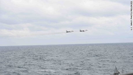 A pair of Russian Su-24s pass within close proximity of the guided-missile destroyer USS Porter while the ship conducts routine maritime operations in international waters.