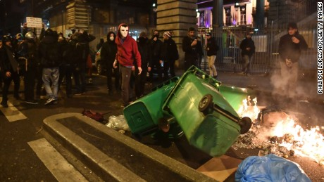 Protesters stand in front of burning trash bins.