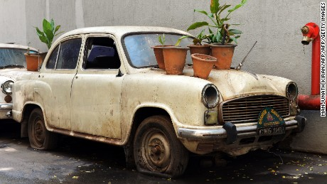 """An old defunct Ambassador """"State Car"""" hosts plant bearing pots at the basement of a government building in Bangalore on May 30, 2014 -- the year production was stopped."""