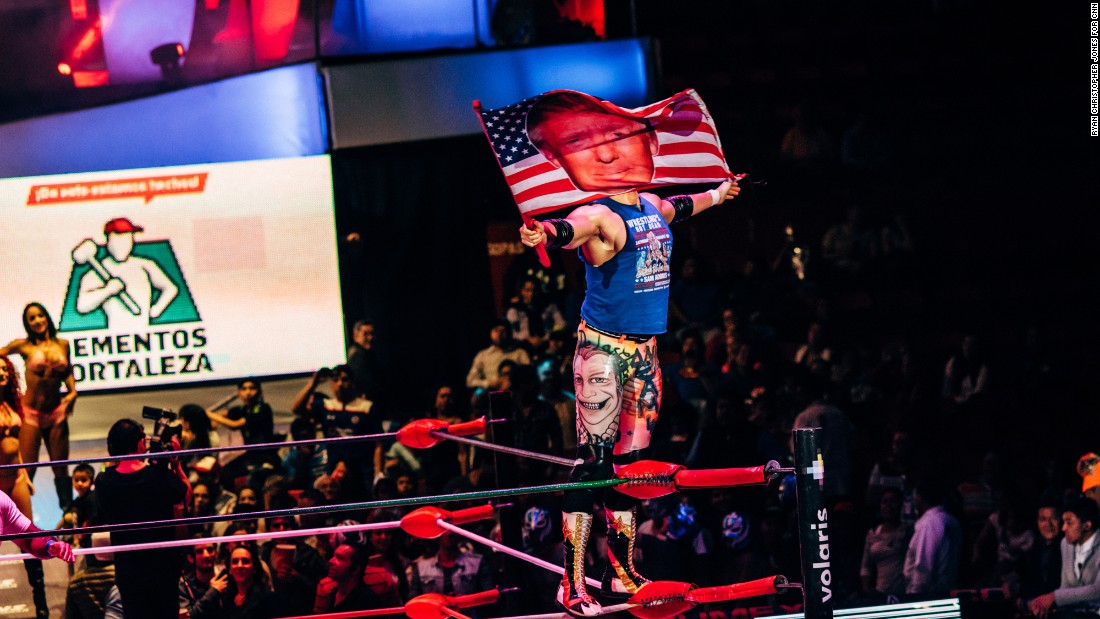 Lucha Libre wrestler Sam Adonis waves a Donald Trump flag as he is introduced to the crowd at Arena Mexico on Sunday, February 12.