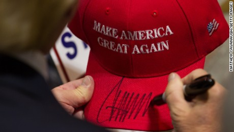 Donald Trump signs a hat after speaking at a campaign rally.