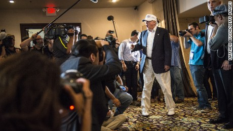 "Donald Trump visits the US-Mexico border wearing a ""Make America Great Again"" hat and golf shoes."
